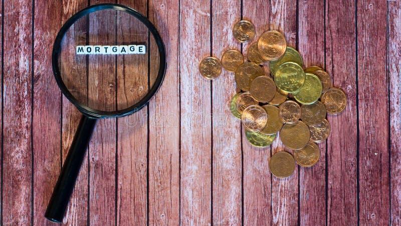 Préstamo de hipoteca, lupa y monedas fotos de archivo