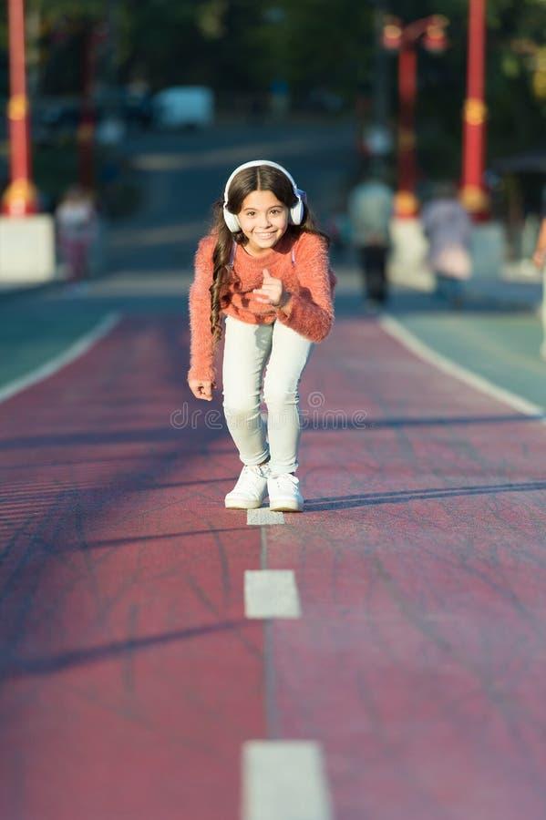 Prêt à fonctionner Position de petite fille sur la ligne de début tout en courant extérieur La petite fille écoutent musique Joue images stock