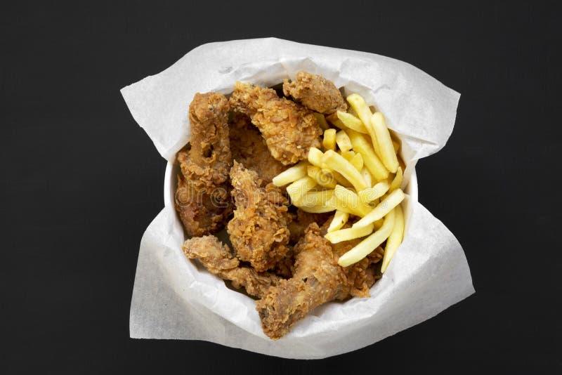 Prêt-à-manger savoureux : les jambes de poulet frit, les ailes épicées, les pommes frites et les doigts de poulet dans la boîte d photographie stock libre de droits