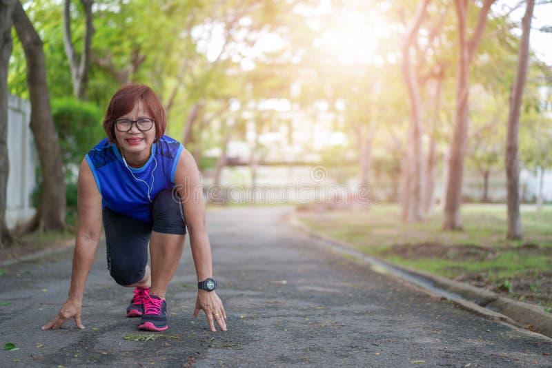 Prêt heureux de femme asiatique supérieure à commencer à courir photographie stock