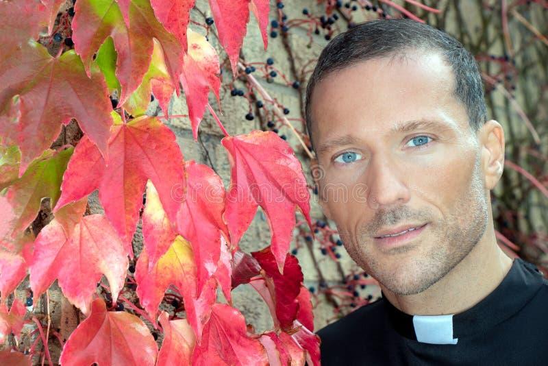 Prêtre beau avec des poses évidentes de collier pour le portrait à côté du lierre rouge de plante grimpante de Virginie photo stock