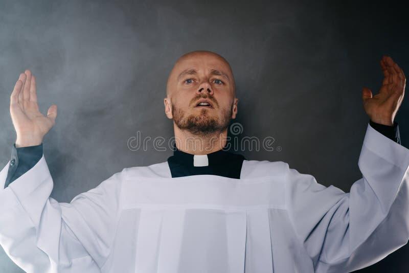Prêtre catholique dans le surplis blanc et chemise noire avec la prière de collier d'ecclésiastique images stock
