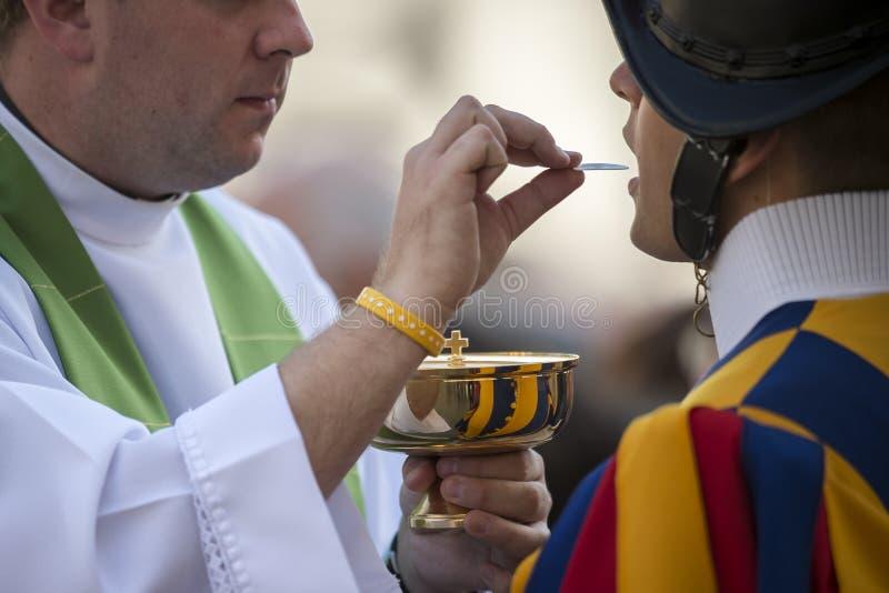 Prêtre catholique donnant à une garde suisse la sainte communion photographie stock
