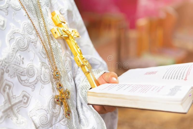 Prêtre dans l'église près du trône avec la croix images stock