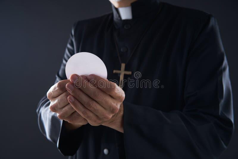 Prêtre de hostia de gaufrette de communion dans des mains images libres de droits