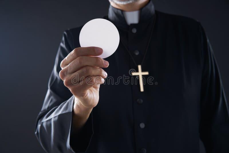 Prêtre de hostia de gaufrette de communion dans des mains photo libre de droits