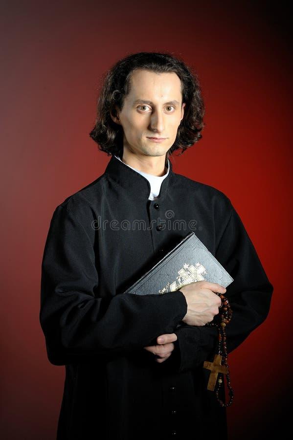Prêtre de prière avec la croix en bois et la bible sainte photographie stock libre de droits