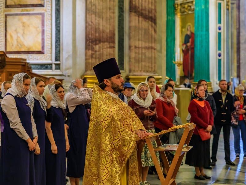Prêtre orthodoxe russe dans l'habillement traditionnel servant dans la cathédrale orthodoxe russe d'Isaac de saint dans le St Pet image libre de droits