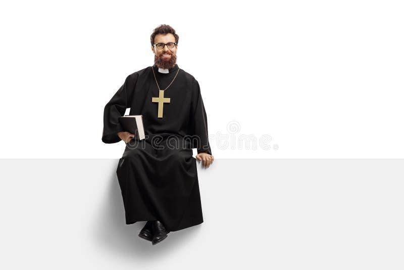 Prêtre s'asseyant sur un panneau et tenant une bible photo libre de droits