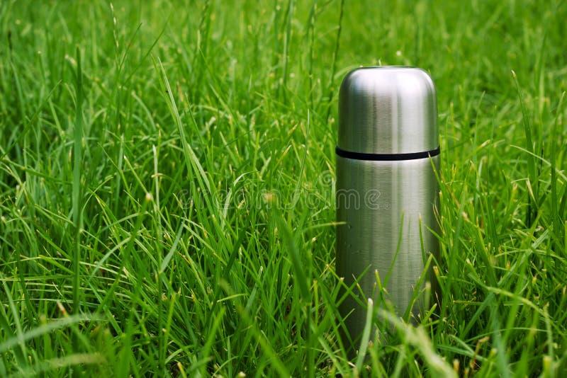 Próżnia izolował stalową termos butelkę w zielonej trawie przy lato pinkinem fotografia stock
