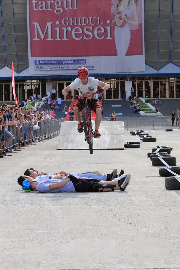 Próbny rowerzysta skacze nad 4 facetami fotografia royalty free