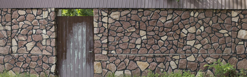 Próbobranie naturalny kamienia ogrodzenie z starą drewnianą bramą obrazy stock
