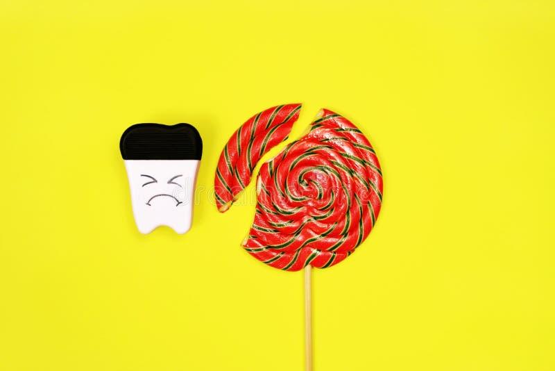 Próchnicy ząb i lizak na żółtym tle Zęby Czyści pojęcie obraz stock