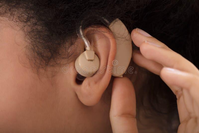 Prótesis de oído de la mujer que desgasta fotografía de archivo