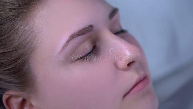Próximo acima da cara da senhora, mulher que relaxa no salão de beleza, procedimentos da cosmetologia fotografia de stock