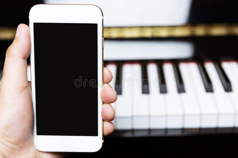 Próximo acima da mão dos povos que guarda o telefone esperto móvel branco com placa imagens de stock royalty free