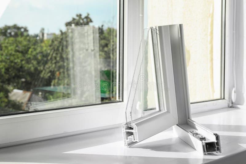 Prövkopia av den moderna fönsterprofilen på fönsterbräda royaltyfri bild