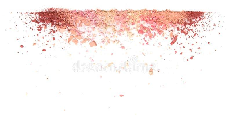 Prövkopior av den torra rodnaden, pulver, bronzers och highlighteren spridde i en linje som isolerades på en vit bakgrund royaltyfri foto