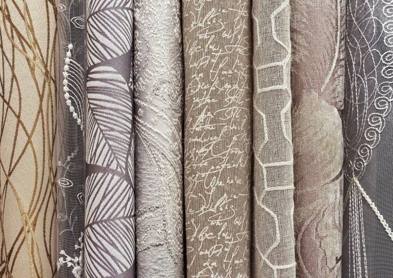 Prövkopior av gardiner i beiga-brunt palett Bakgrund och textur av beige tyg för gardiner arkivbild