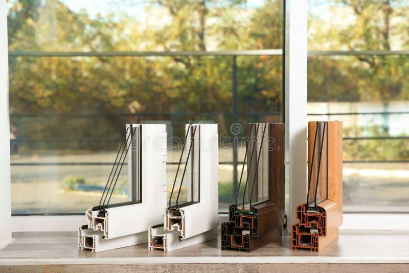Prövkopior av moderna fönsterprofiler på fönsterbräda inomhus royaltyfria bilder