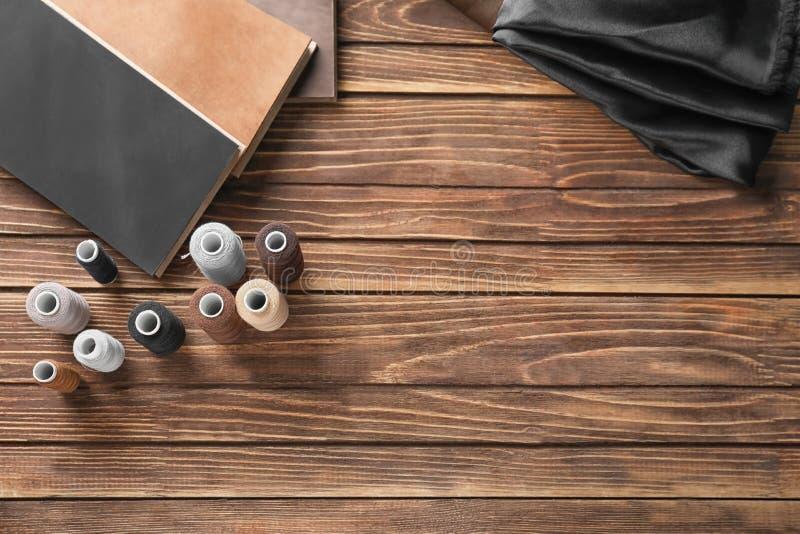 Prövkopior av tyg- och sömnadtrådar på träbakgrund arkivfoton