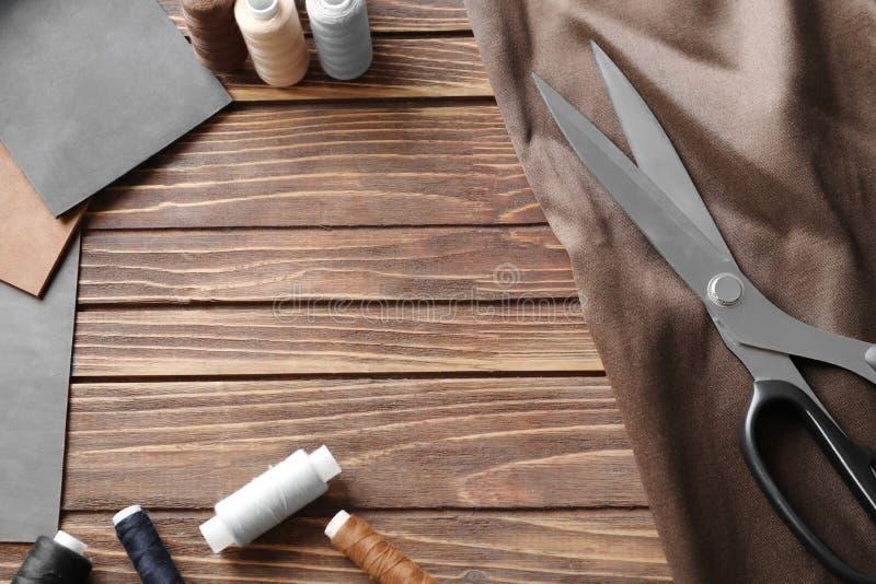 Prövkopior av tyg- och sömnadtrådar på träbakgrund royaltyfri foto