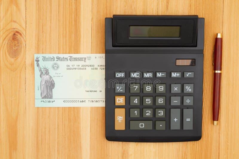 Prüfen Sie, ob eine Bundessteuerrückerstattung oder eine Sozialversicherungszahlung mit einem Rechner und einem Schreibtisch erfo stockbild