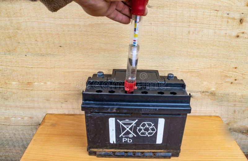 Prüfung der Elektrolytdichte der Batterie mit einem Hydrometer lizenzfreie stockfotografie