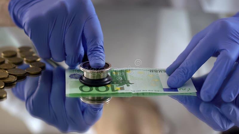 Prüfung der Eurobanknote mit Stethoskop, Konzept der Inflation, Symptome stockbild