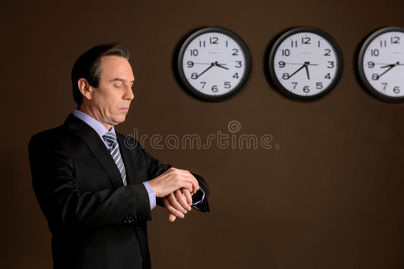 Prüfung der Zeit. Überzeugter reifer Geschäftsmann, der sein w betrachtet lizenzfreies stockbild