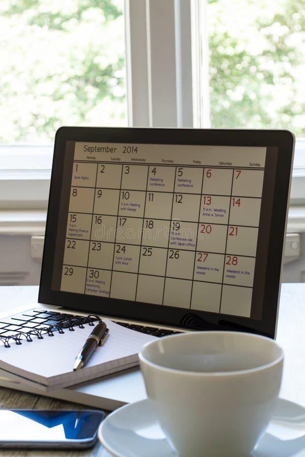 Prüfung von Monatstätigkeiten im Kalender im Laptop stockfoto