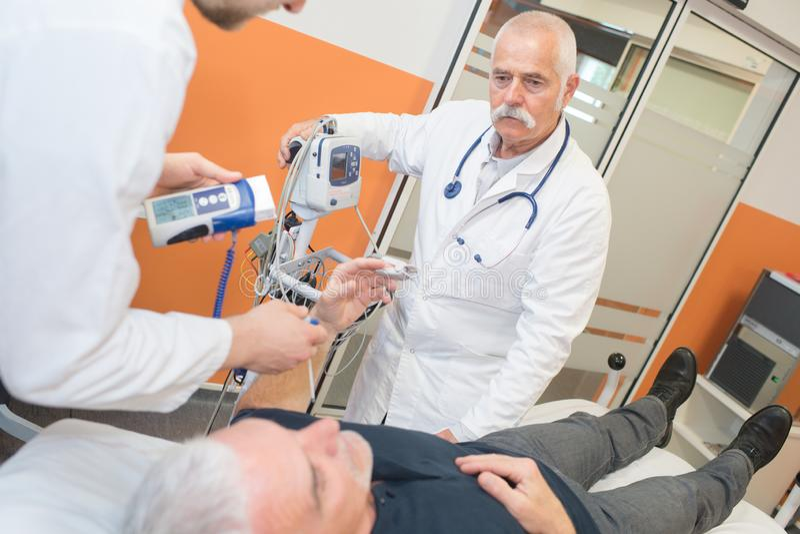 Prüfungsälterer Mann diabetes männlichen Doktors im Krankenhaus lizenzfreies stockfoto