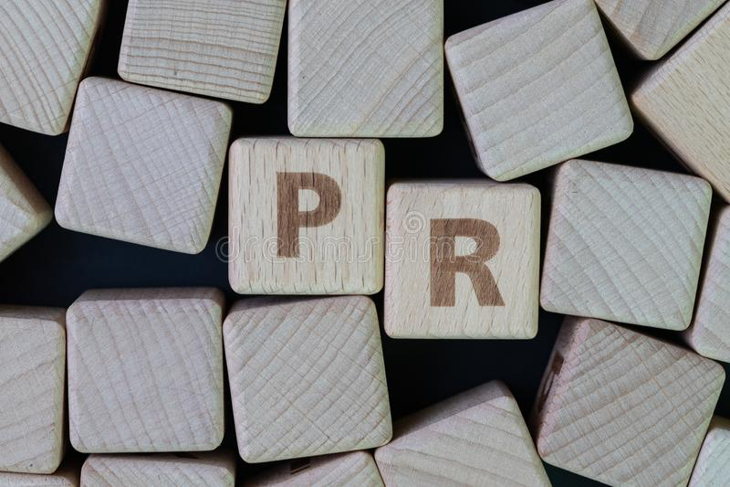 PR、公共关系公司或者公司通信概念,与字母表的立方体木块结合在黑色的词PR 图库摄影