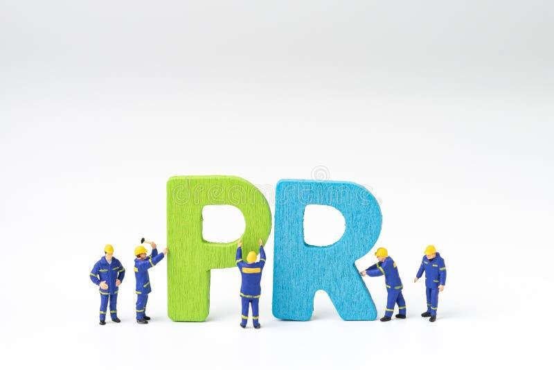 PR,公共关系概念,微型人职员帮助buildi 库存照片