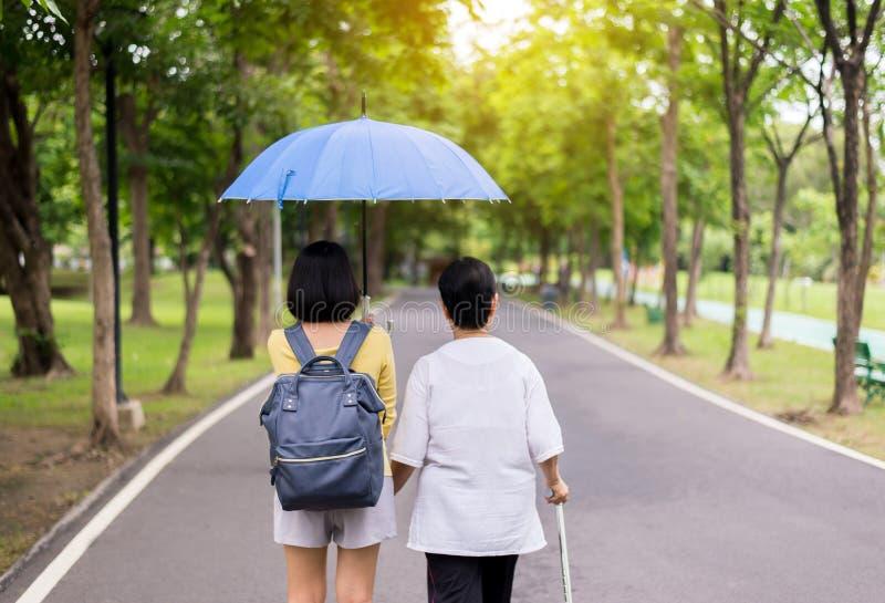 Pr?b starsze azjatykcie kobiety chodzi robi? treningowi z kijem przy jawnym parkiem, c?rka bior? opiek? i poparcie zdjęcia stock