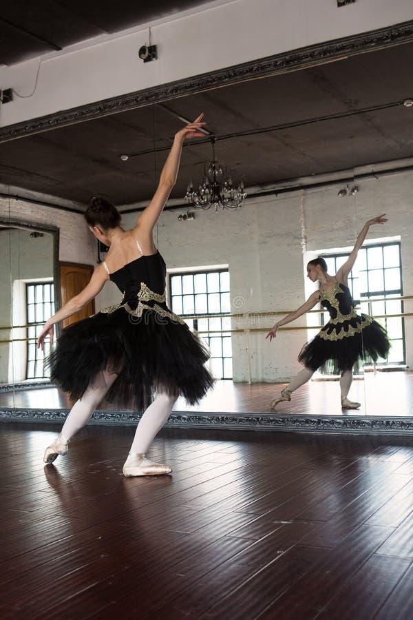 Pr?by balerina w sali Bia?e ?ciany, ciemna drewniana pod?oga, ciemny sufit, pi?kni ?wieczniki, odbicie zdjęcia royalty free