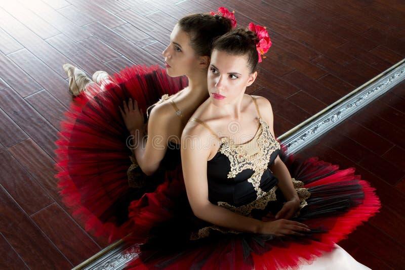 Pr?by balerina w sali Lekki bia?y pok?j, drewniana pod?oga, ampu? lustra Balerina odbijaj?ca w lustrze obraz royalty free