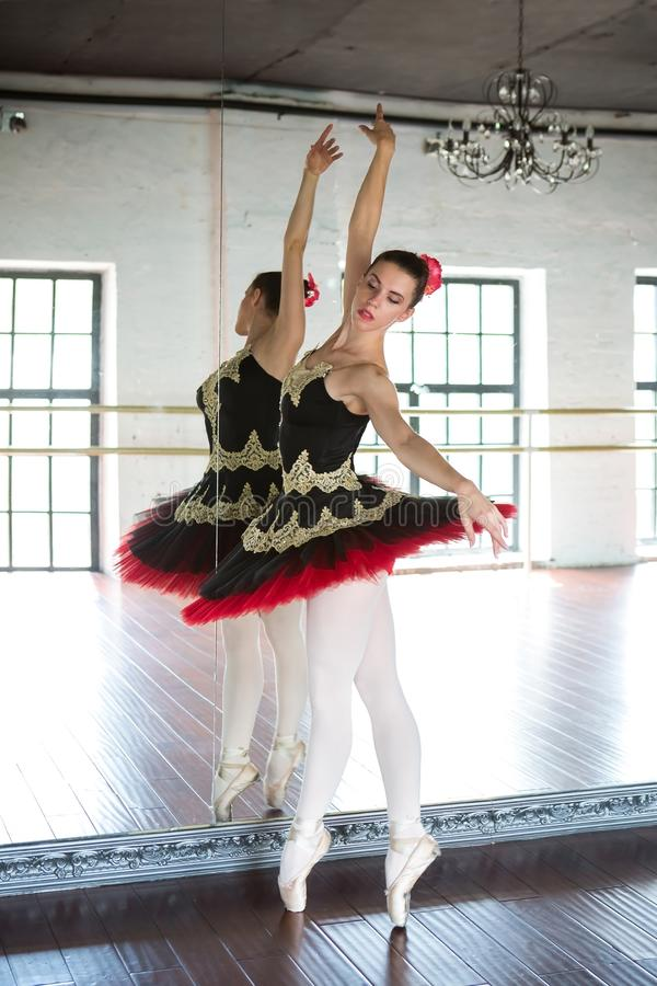 Pr?by balerina w sali Lekki bia?y pok?j, drewniana pod?oga, ampu? lustra Balerina odbijaj?ca w lustrze zdjęcia royalty free