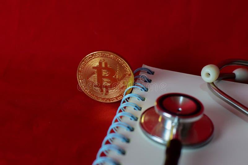 Pr?gen Sie bitcoin, Notizbuch, Stethoskop und eine Lupe, die auf rotem Hintergrund lokalisiert wird lizenzfreie stockfotografie
