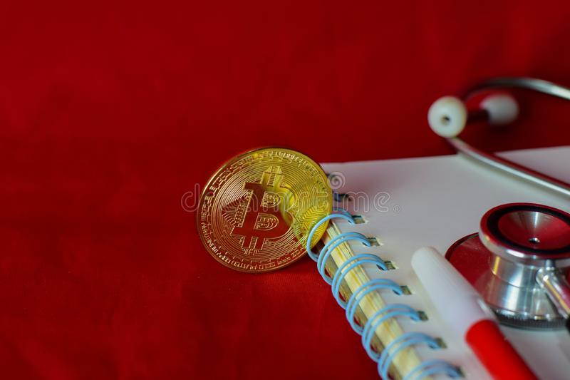 Pr?gen Sie bitcoin, Notizbuch, Stethoskop und eine Lupe, die auf rotem Hintergrund lokalisiert wird lizenzfreie stockfotos