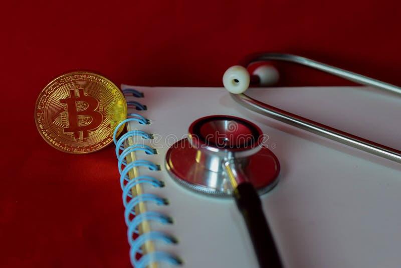 Pr?gen Sie bitcoin, Notizbuch, Stethoskop und eine Lupe, die auf rotem Hintergrund lokalisiert wird stockfoto