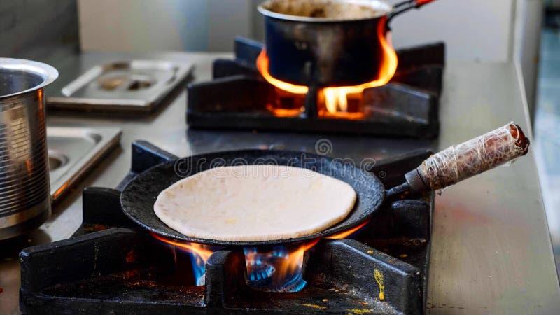 Pr?paration du paratha indien d'aloo dans une po?le sur la cuisini?re ? gaz images libres de droits