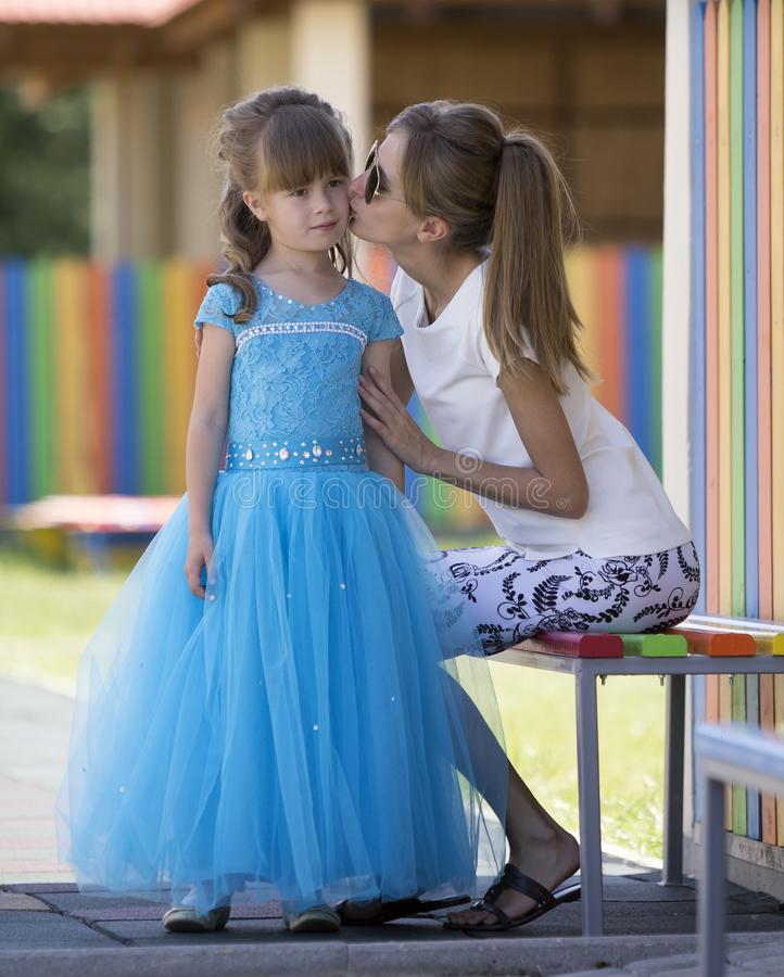 PR pequeno de beijo de sorriso louro magro novo da mãe, da tia ou da irmã imagem de stock