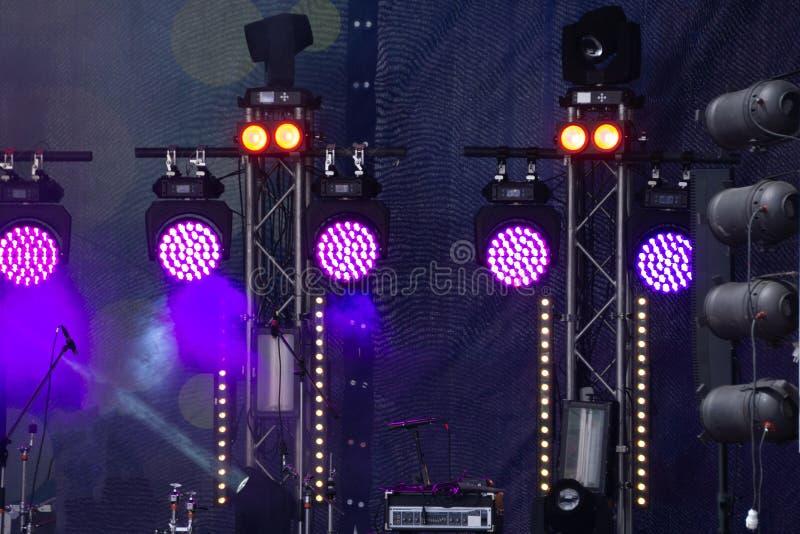 Pr?sentez les lumi?res Plusieurs projecteurs dans l'obscurit? Gr?ve pourpre de projecteur par l'obscurit? photographie stock