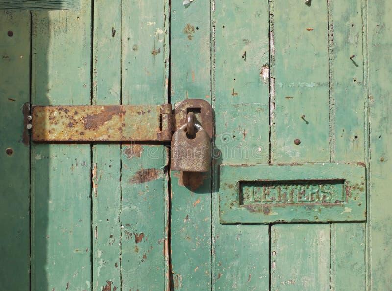 pr?ximo acima de uma porta de madeira velha com pintura desvanecida verde e uma caixa fechado oxidada do cadeado e a velha do met imagens de stock