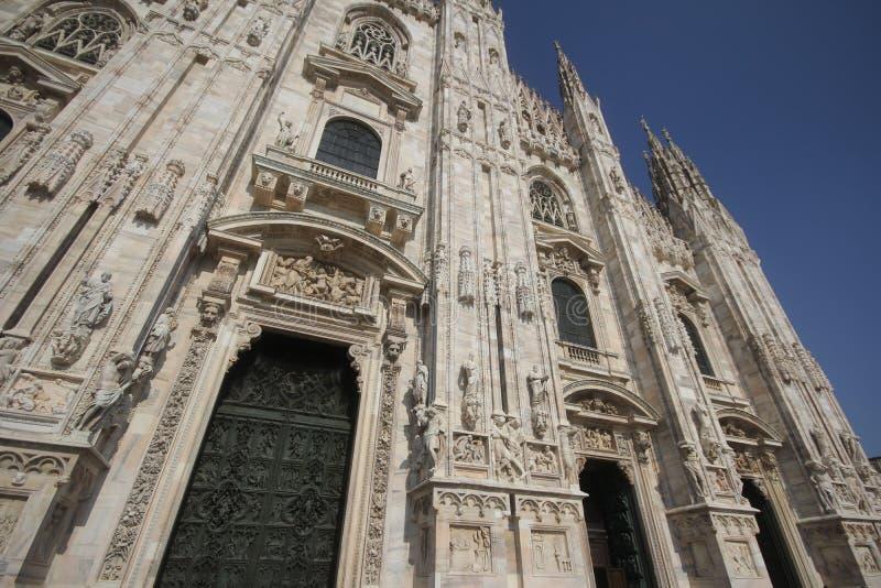 A praça del Domo Milão, igreja arquitetónica branca famosa sob o céu azul em Milão, a igreja a maior da catedral em Itália foto de stock royalty free