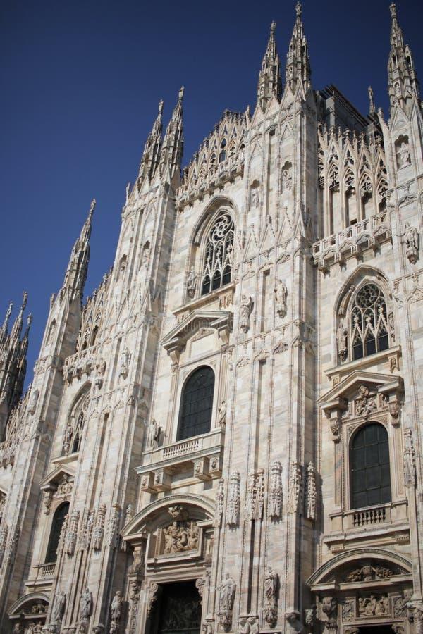 A praça del Domo Milão, igreja arquitetónica branca famosa sob o céu azul em Milão, a igreja a maior da catedral em Itália fotografia de stock royalty free