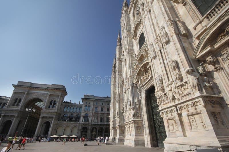 A praça del Domo Milão, igreja arquitetónica branca famosa sob o céu azul em Milão, a igreja a maior da catedral em Itália fotografia de stock