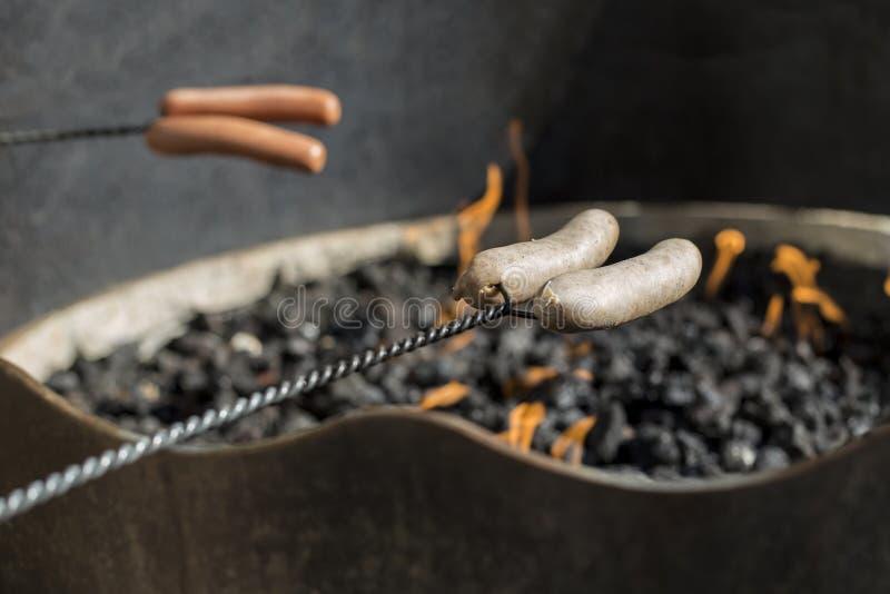 Prażak kiełbasy nad ogniskiem i hot dog zdjęcie royalty free