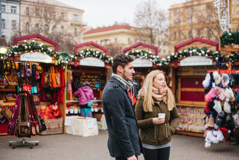 Praag, 15 December, 2016: De Europese de paarman en vrouw in de Kerstmismarkt drinken heet overwogen wijn en horloge stock foto